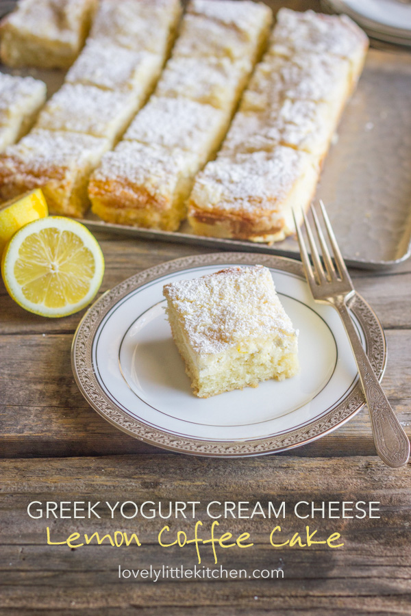Greek Yogurt Cream Cheese Lemon Coffee Cake square piece on a plate with a fork, and the rest of the sliced cake on a serving tray in the background.