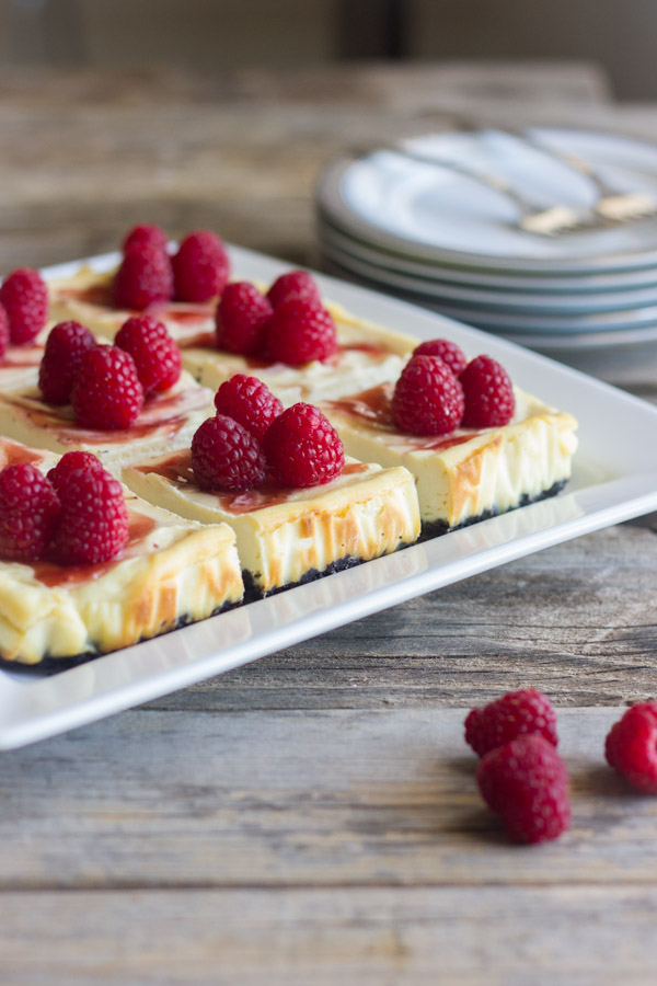 Raspberry Swirl Cheesecake Bars arranged on a serving plate, with a pile of plates in the background with forks on top.