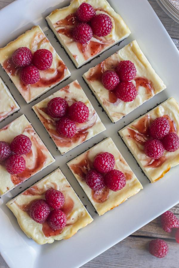Raspberry Swirl Cheesecake Bars arranged on a serving plate.