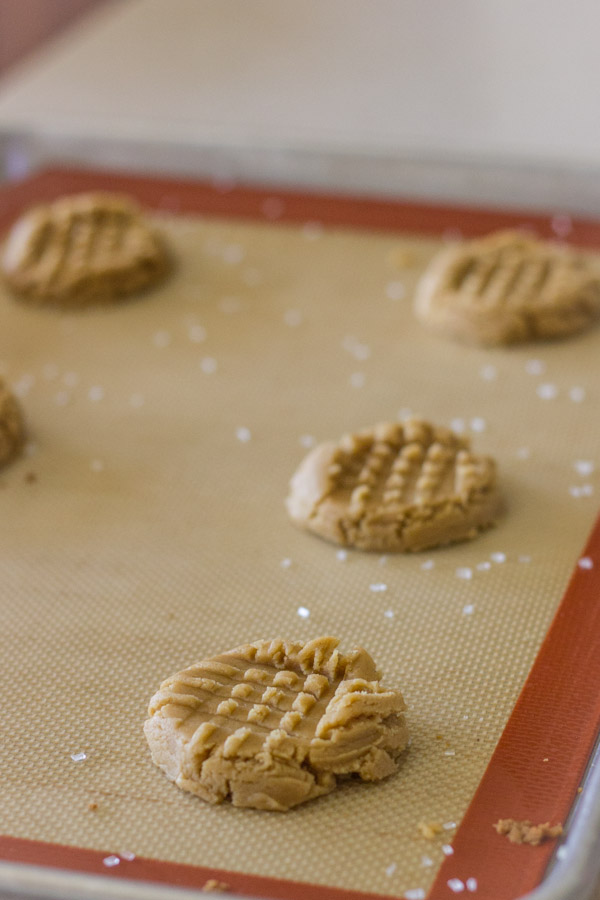 Brown Butter Peanut Butter Cookie dough on a Silpat lined backing sheet, pressed down with a crosshatch pattern and a sprinkle of sparkling sugar.