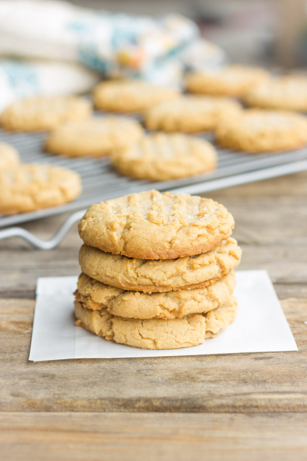 Brown Butter Peanut Butter Cookies stacked in a pile of four with more cookies on a cooling rack in the background.
