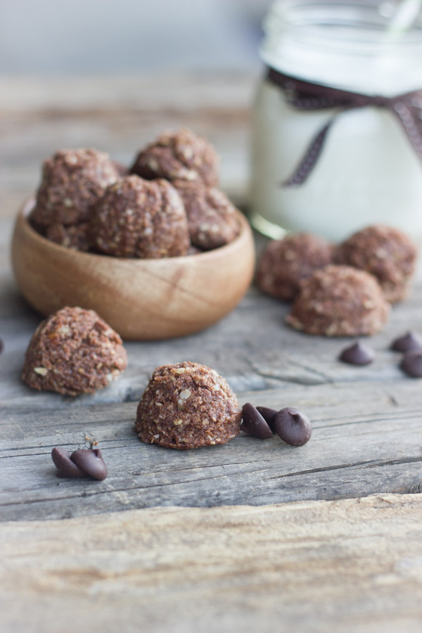 Chocolate Almond Energy Bites piled in a bowl with a few outside of the bowl along with a few chocolate chips and a glass of milk in the background.