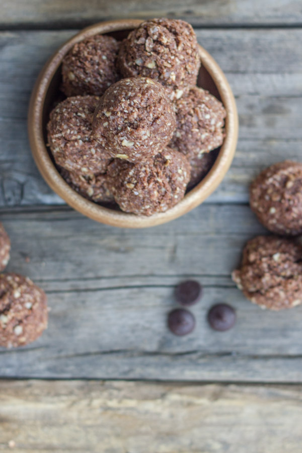 Chocolate Almond Energy Bites piled in a bowl with a few outside of the bowl along with a few chocolate chips.