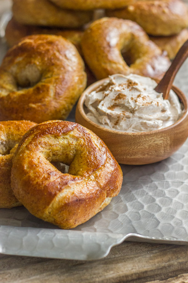 Whole Wheat Soft Pretzel Bagels stacked on a serving platter with a small bowl of Cinnamon Sugar Cream Cheese.