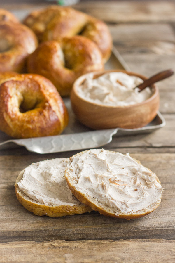 Whole Wheat Soft Pretzel Bagel sliced in half with Cinnamon Sugar Cream Cheese spread on it, and a serving platter of bagels and cream cheese in the background.