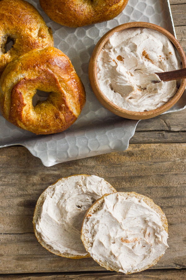 Whole Wheat Soft Pretzel Bagel sliced in half with Cinnamon Sugar Cream Cheese spread on it, and a serving platter of bagels and cream cheese next to it.