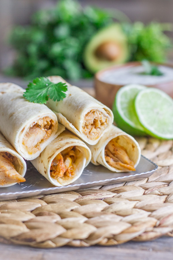 Baked Honey Lime Chicken Taquitos stacked on a serving platter with a bowl of Cilantro Lime Cream in the background.