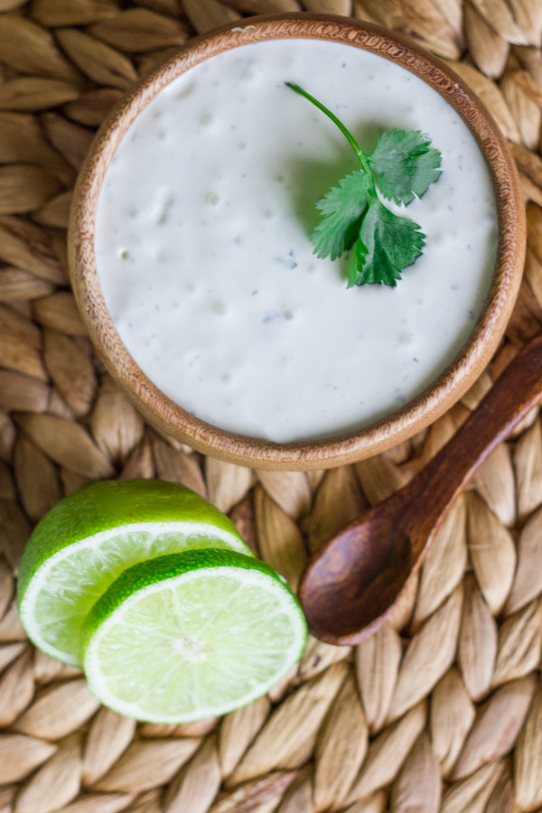 A bowl of Cilantro Lime Cream with a sliced lime and small spoon next to it.