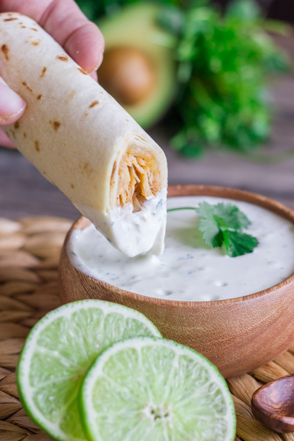 Baked Honey Lime Chicken Taquito being dipped into a small bowl of Cilantro Lime Cream, with a sliced lime next to the bowl.