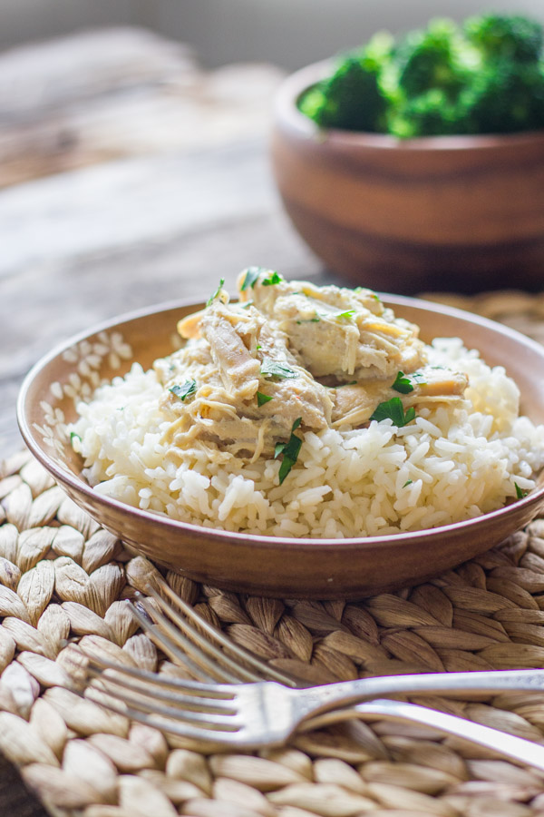 Easy Creamy Crockpot Chicken on top of a bowl of cooked rice.