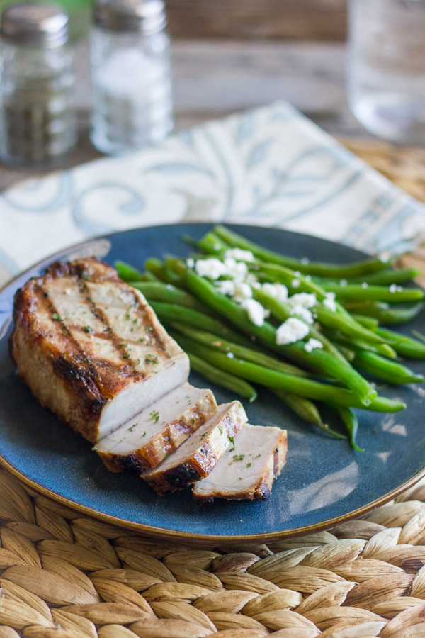 Marinated Grilled Pork Chop on a plate with green beans topped with feta.