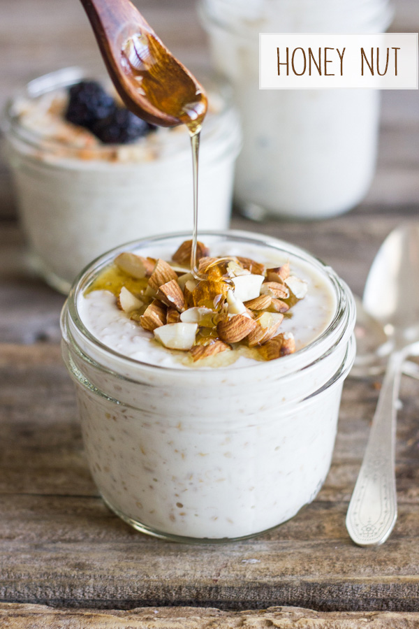 Overnight Steel Cut Oatmeal with almonds in a glass jar with honey being drizzled on top, and two other jars of Overnight Steel Cut Oatmeal in the background.
