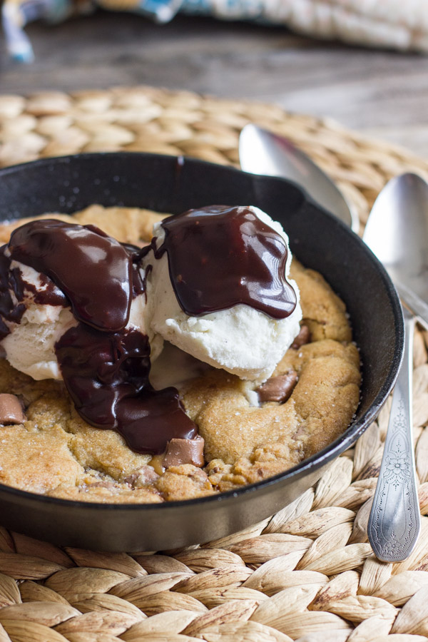 Salted Rolo Chip Pizookie in a small cast iron skillet, topped with vanilla ice cream and Homemade Hot Fudge.
