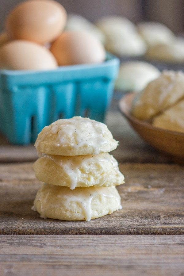 Soft Ricotta Cookies With Vanilla Bean Glaze stacked in a pile of three, with a carton of eggs and more cookies in the background.