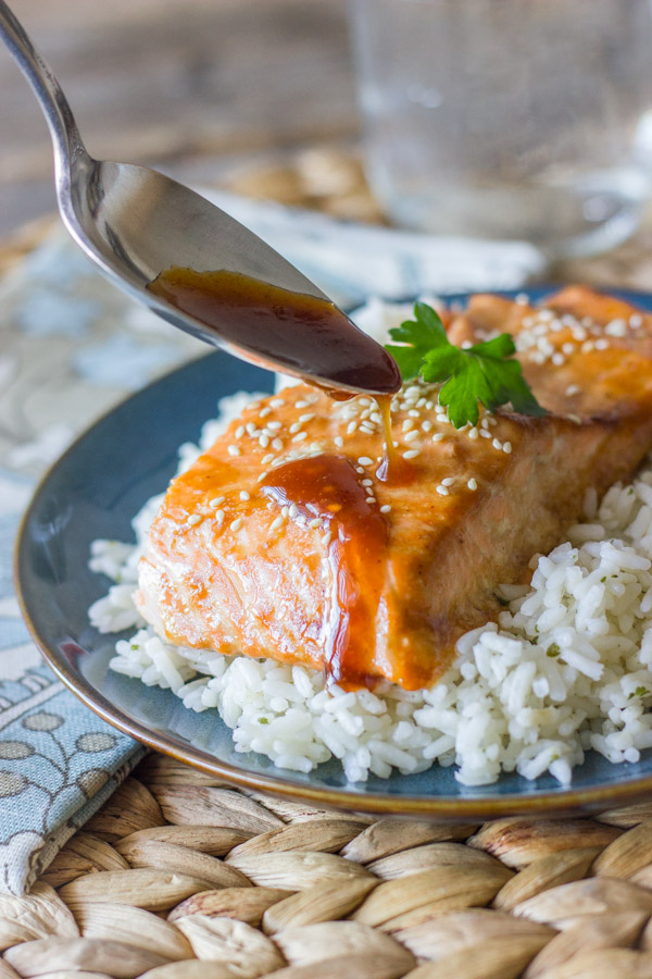 Teriyaki Glazed Salmon served on top of a bed of white rice, with a spoon drizzling the teriyaki glaze on top of the salmon.
