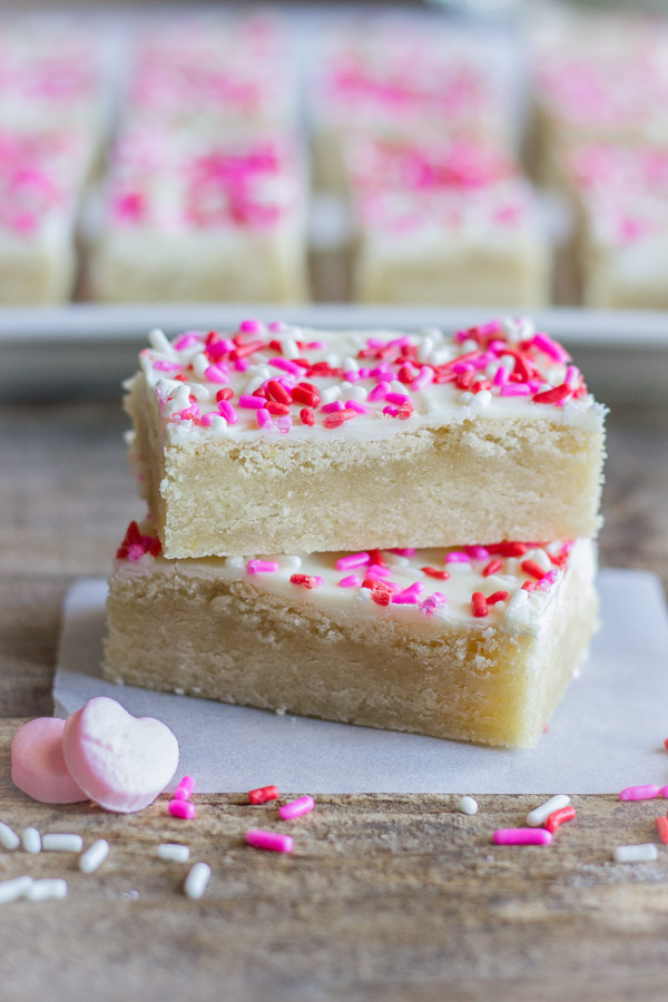 Two Easy White Chocolate Sugar Cookie Bars stacked on top of each other, with sprinkles and two candy hearts near by.