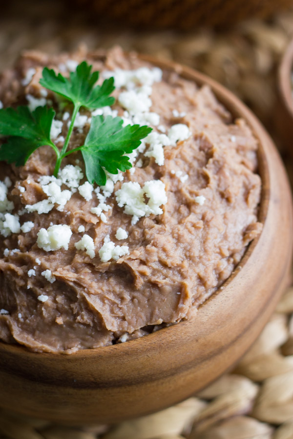 Healthy Crockpot Refried Beans in a bowl topped with queso fresco and cilantro.