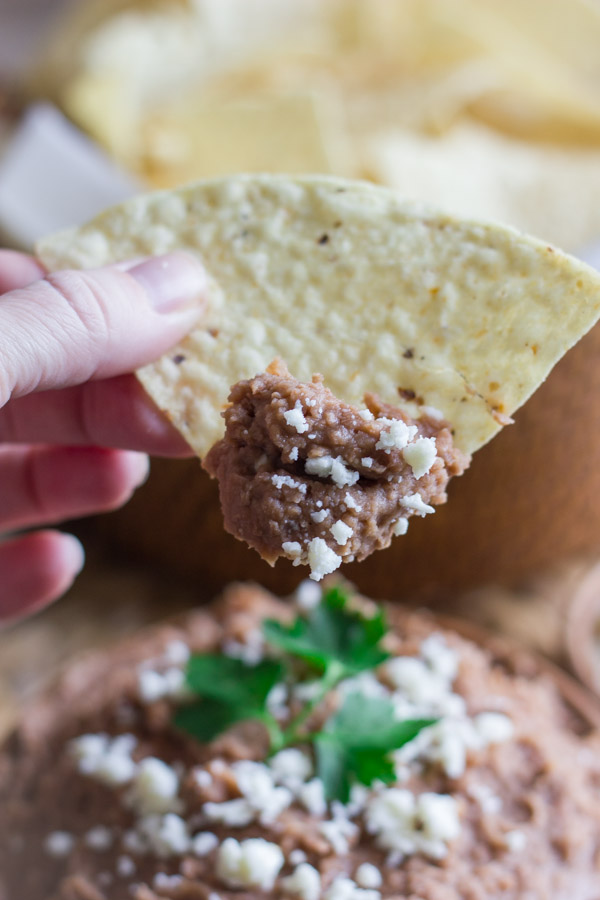 A tortilla chip that has been dipped in a bowl of Healthy Crockpot Refried Beans topped with queso fresco and cilantro.
