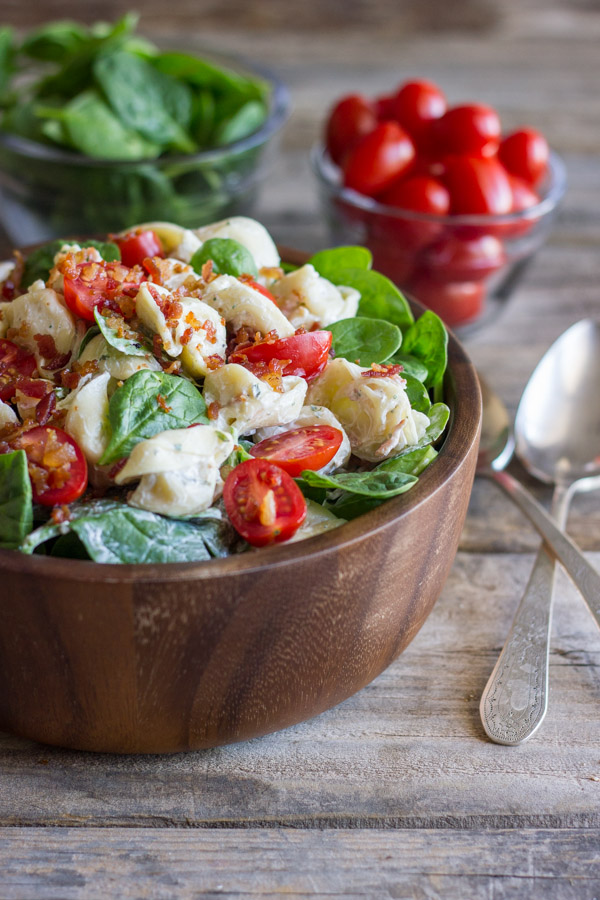 BLT Pasta Salad in a bowl, with a glass dish of spinach, a glass dish of grape tomatoes and two spoons next to the bowl.