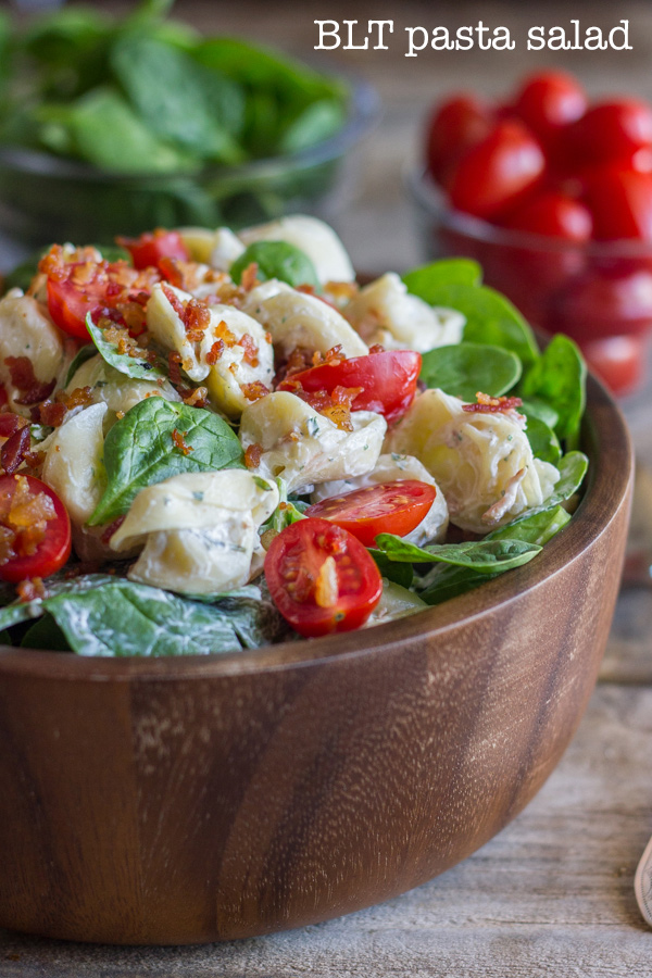 BLT Pasta Salad in a bowl, with a glass dish of spinach and a glass dish of grape tomatoes in the background.