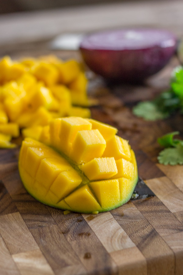 A mango diced on a cutting board, with a half red onion and cilantro in the background.