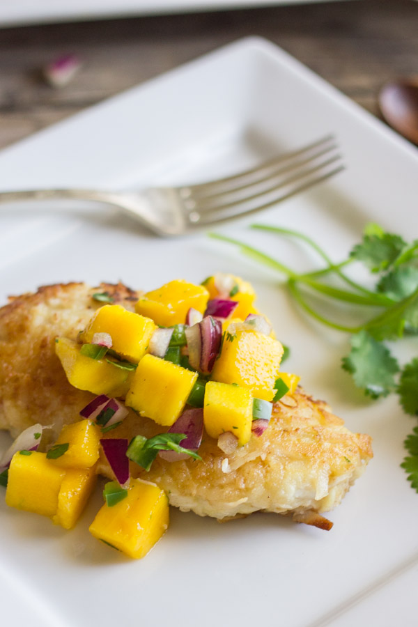 Coconut Crusted Chicken With Mango Salsa on top, on a plate with a fork and cilantro.