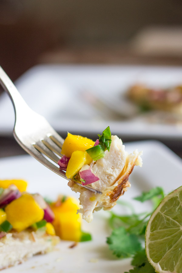 Coconut Crusted Chicken With Mango Salsa bite on a fork with the plated meal in the background.