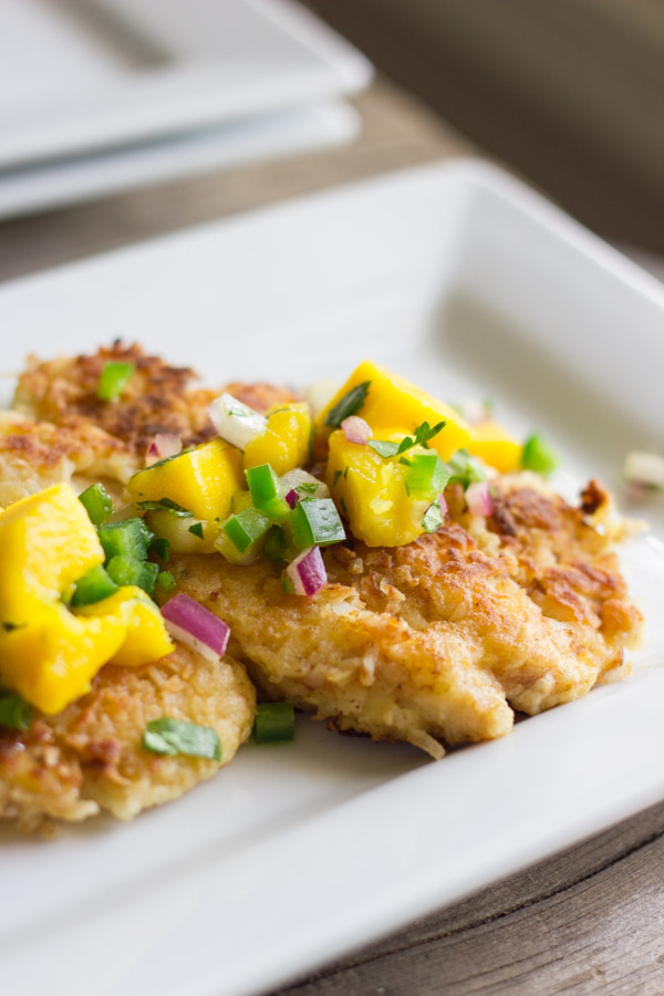 Coconut Crusted Chicken With Mango Salsa on top, on a plate.