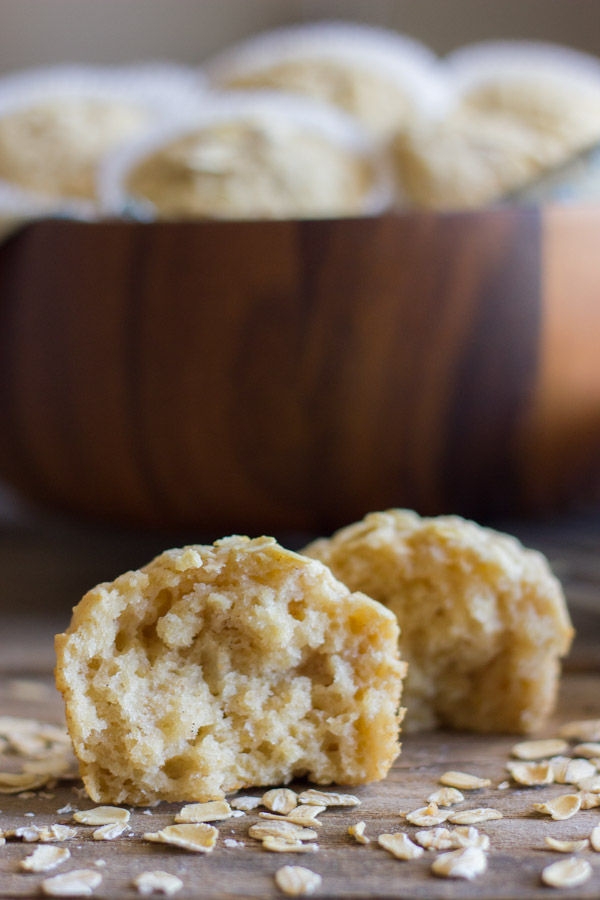 Healthy Applesauce Oat Muffin halved with oats sprinkled around it, and more muffins in a large bowl in the background.