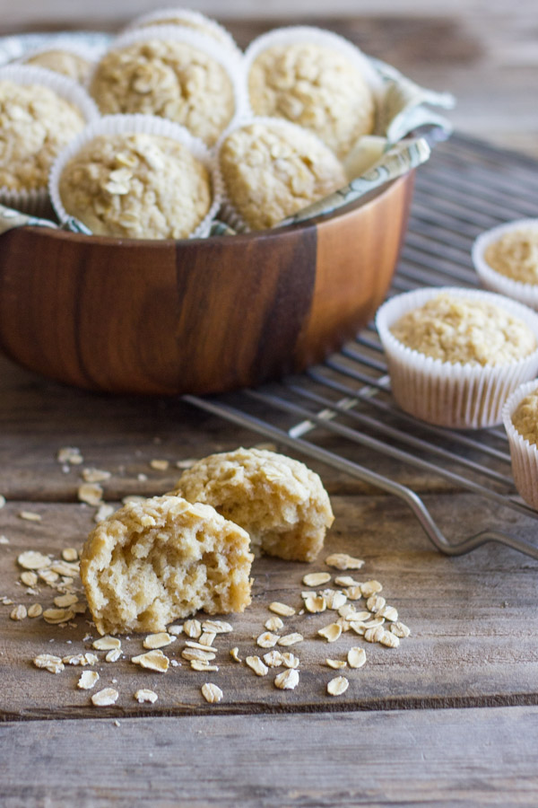 Healthy Applesauce Oat Muffin halved with oats sprinkled around it, and more muffins in a large bowl and on a cooling rack in the background.