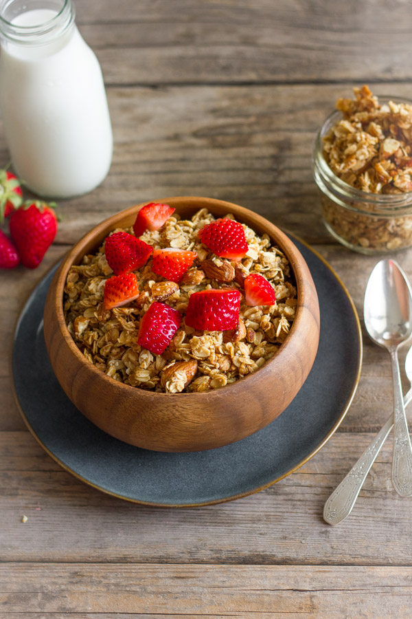 Homemade Coconut Oil Honey Almond Granola in a bowl with strawberry pieces on top, with a glass jar of milk and a small glass jar of the granola next to it.