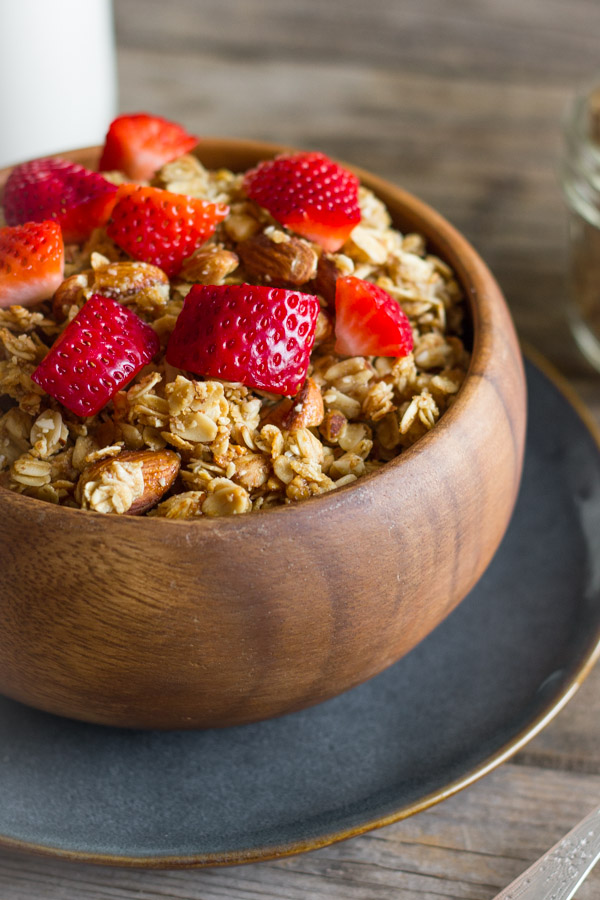 Homemade Coconut Oil Honey Almond Granola in a bowl with strawberry pieces on top.