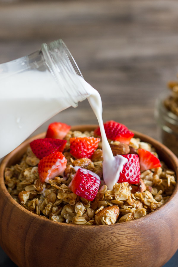 Homemade Coconut Oil Honey Almond Granola in a bowl with strawberry pieces on top, with a glass jar of milk being poured over it.