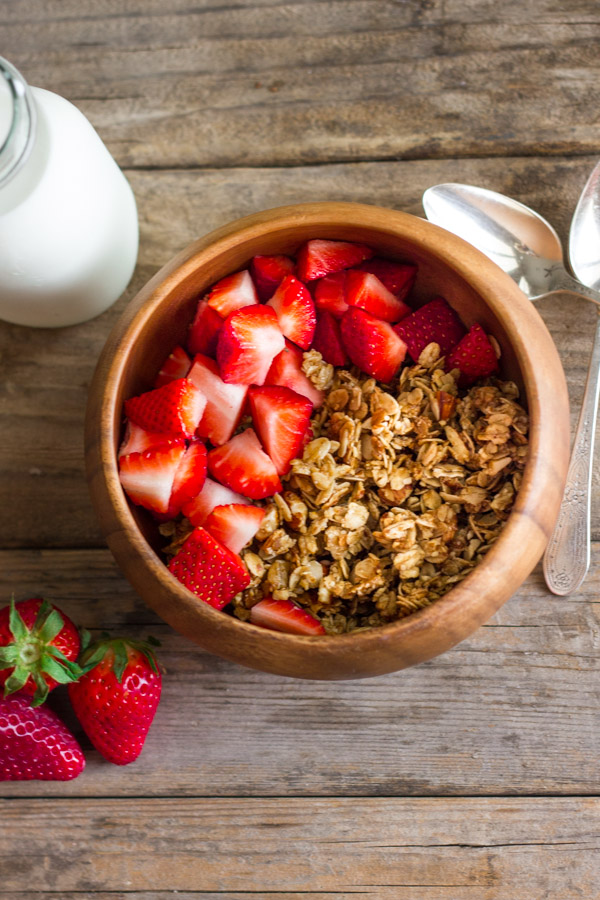 Homemade Coconut Oil Honey Almond Granola in a bowl with cut up strawberries, with a glass jar of milk, three whole strawberries and two spoons next to it.
