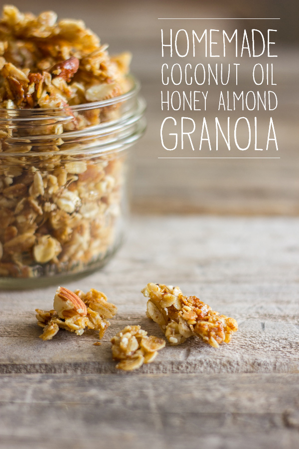 Homemade Coconut Oil Honey Almond Granola in a small glass jar with a few chunks spilled out next to it.