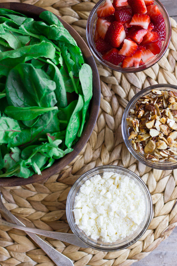 A large bowl of spinach, a small glass dish of strawberries, a small glass dish of sugared almonds, and a small glass dish of Feta cheese.