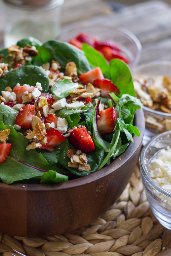 Strawberry and Spinach Salad with Almond Vinaigrette in a bowl, with a small glass dish of strawberries, a small glass dish of sugared almonds, and a small glass dish of Feta cheese next to it.