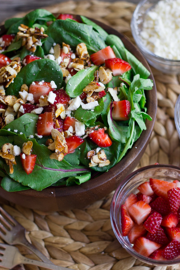 Strawberry and Spinach Salad with Almond Vinaigrette in a bowl, with a small glass dish of strawberries and a small glass dish of Feta cheese next to it.