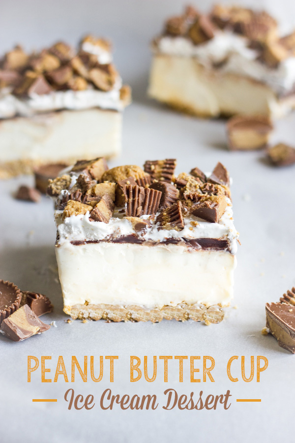 Peanut Butter Cup Ice Cream Dessert square piece with bits of peanut butter cups around it and two more square pieces of the dessert in the background.