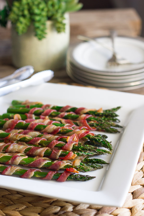 Bacon Wrapped Asparagus on a serving plate, with a stack of plates and forks in the background.