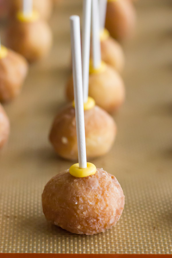 Donut holes with lollipop sticks pressed into them, on a Silpat lined baking sheet.
