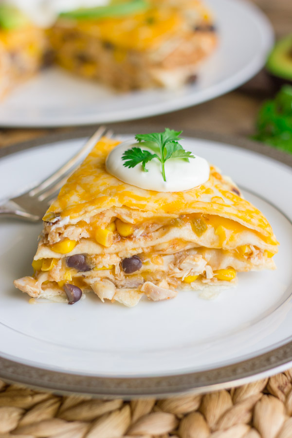 Southwestern Chicken Taco Pie slice topped with sour cream and cilantro, on a plate with a fork.