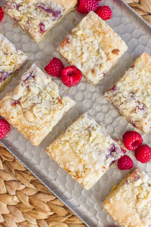 Raspberry Almond Crumb Bar squares on a serving platter with fresh raspberries.