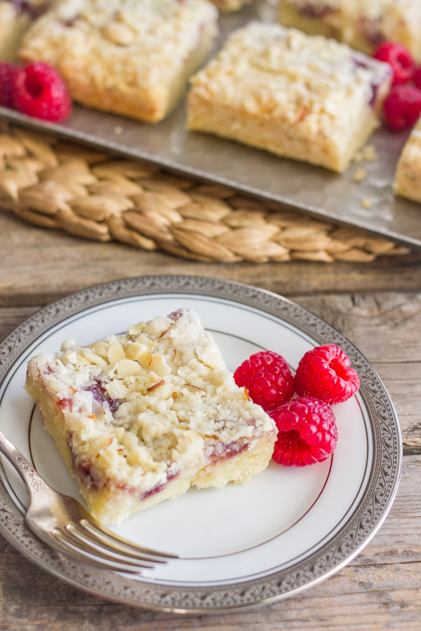 Raspberry Almond Crumb Bar square piece on a plate with fresh raspberries and a fork, with more Raspberry Almond Crumb Bar squares on a serving platter with fresh raspberries in the background.