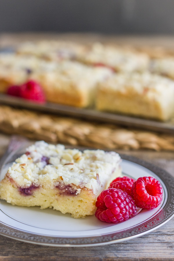 Raspberry Almond Crumb Bar square piece on a plate with fresh raspberries, with more Raspberry Almond Crumb Bar squares on a serving platter with fresh raspberries in the background.