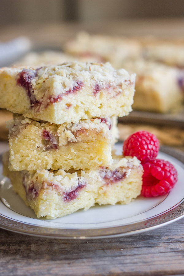 Raspberry Almond Crumb Bar squares stacked in a pile of three on a plate with fresh raspberries next to it.