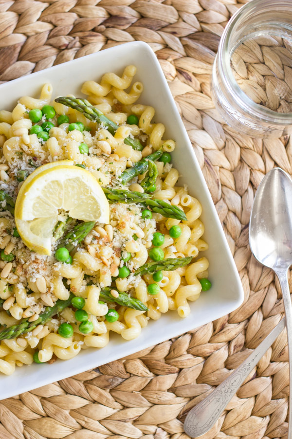 Springtime Pasta With Brown Butter Garlic Cream Sauce in a square bowl, topped with homemade breadcrumbs and a lemon wedge, with a spoon and water glass next to it.