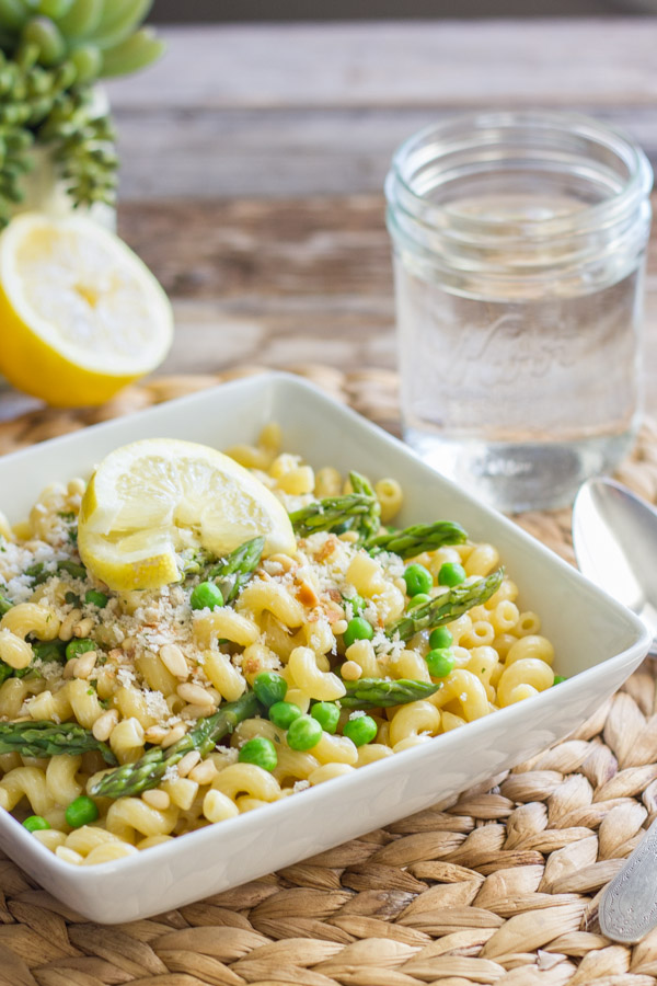 Springtime Pasta With Brown Butter Garlic Cream Sauce in a square bowl, topped with homemade breadcrumbs and a lemon wedge, with a spoon and water glass next to it, and a half of a lemon in the background.