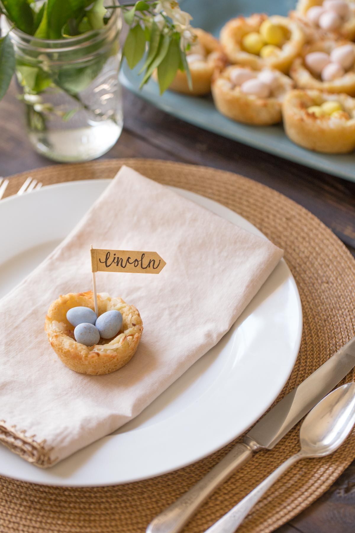 Sugar Cookie Easter Egg Nest with a name flag, sitting on top of a folded napkin on a place setting.