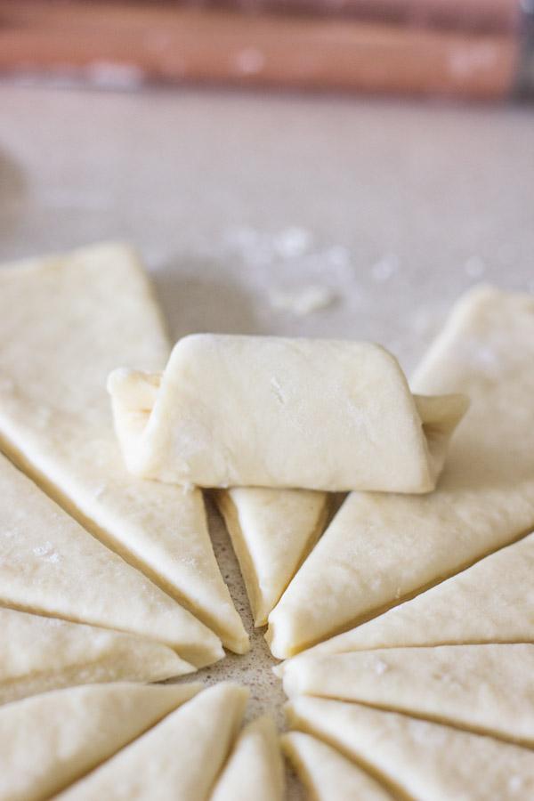 The Best Butterhorn Rolls dough wedge being rolled up.